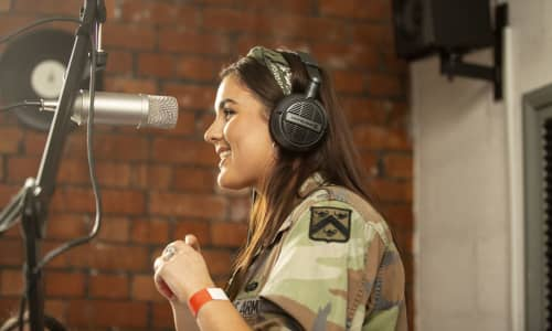 A young woman singing into a microphone