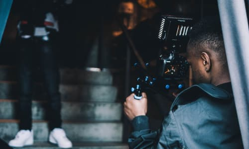 Young black man filming with a video camera