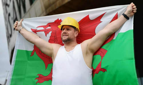Actor Kai Owen wearing a white vest, holding a Welsh flag outside Wales Millennium Centre