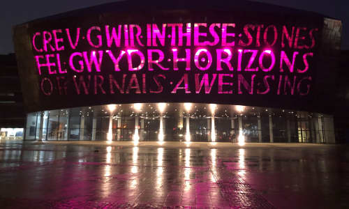 Wales Millennium Centre lit up purple at night