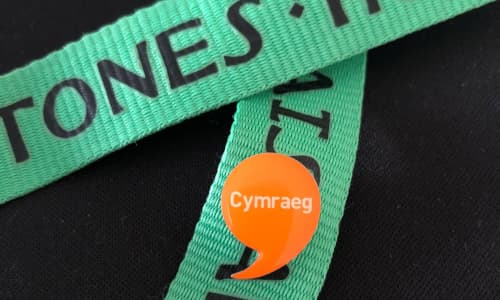 The Work Welsh badge pinned onto a green lanyard