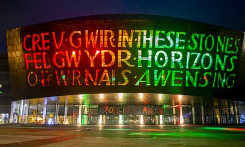 Adeilad Canolfan Mileniwm Cymru wedi'i oleuo'n goch a gwyrdd dros y Nadolig