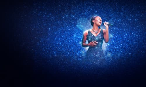 Alexandra Burke wearing a blue dress singing into a microphone on stage during The Bodyguard The Musical