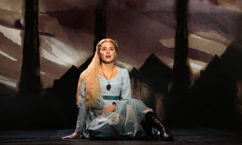 Katie Hall Fantine in a blue dress sat on the floor singing in Les Misérables. Photo: Helen Maybanks