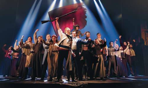 A scene from Les Mis featuring actors on stage holding banners and flags in a defiant manner.
