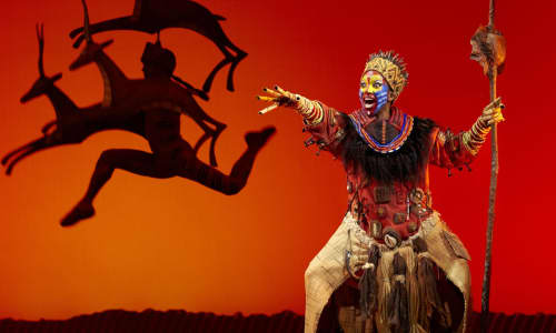 Scene from The Lion King featuring an orange background, gazelles leaping and an African chief with spear singing