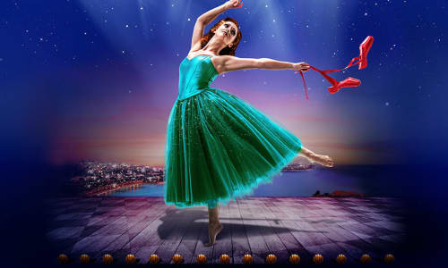 Ballerina in green dress dancing under the spotlight with a pair of red shoes in her hand.
