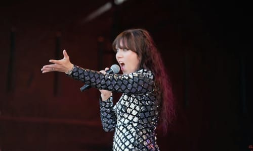Singer wearing a sparkly outfit with her arm outstretched