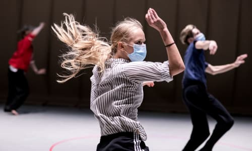 Three dancers from Rambert dancing in protective masks as they rehearse