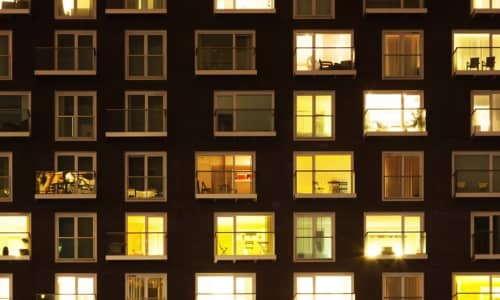 A block of flats at night with the windows lit