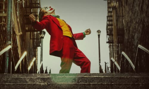 The Joker wearing a red suit laughing