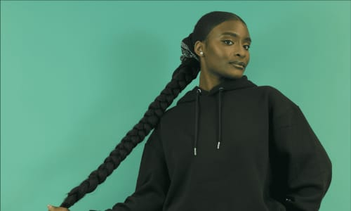 A Black woman holding her long plaited hair