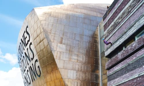 someone abseiling off Wales Millennium Centre