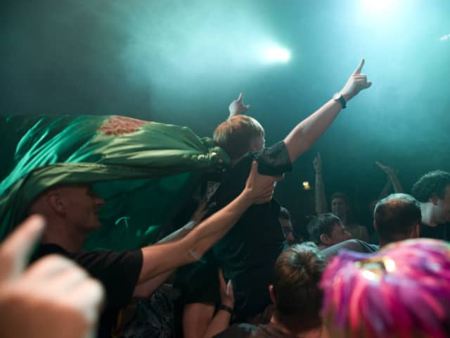 image of people with arms outstretched, enjoying a gig