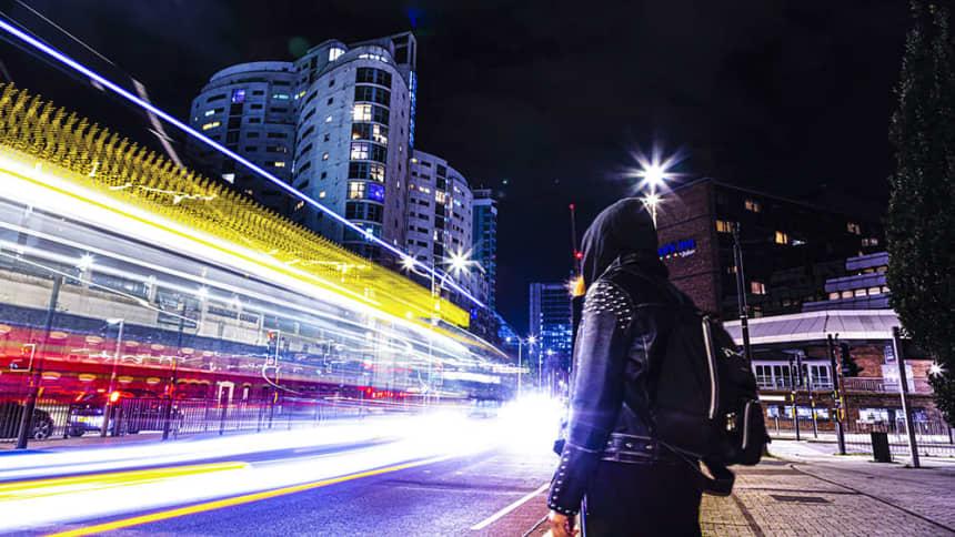 woman stood outside a city at night