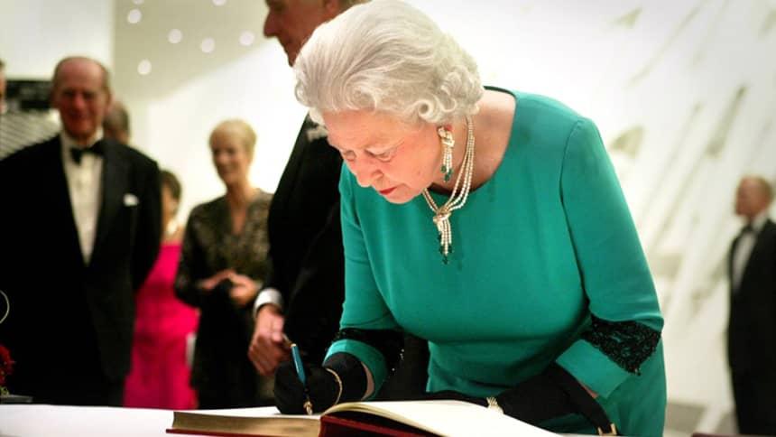 Y Frenhines yn arwyddo'n llyfr ymwelwyr/ The Queen signing our guest book