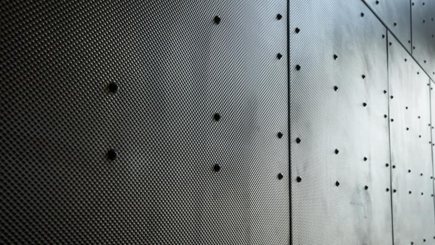 The stainless steel panels used on the roof also feature inside the building but are untreated and feature screws resembling the rivets found on a ship's hull
