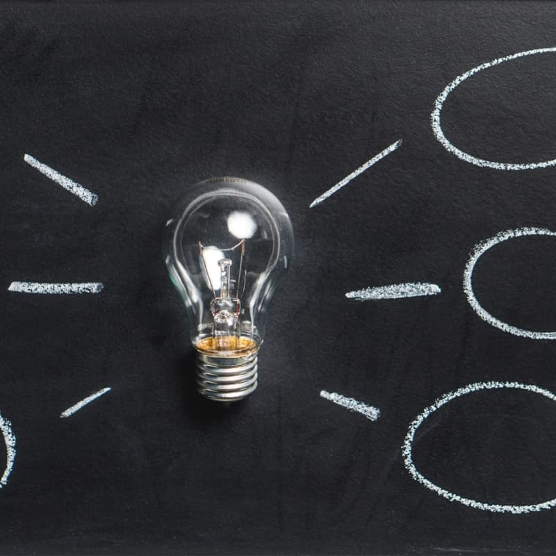 Lightbulb against a black background with idea clouds drawn in chalk next to it