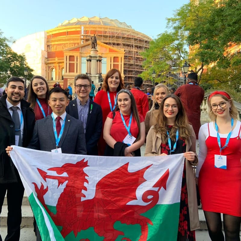 Young people stood outside a building holding a Welsh flag