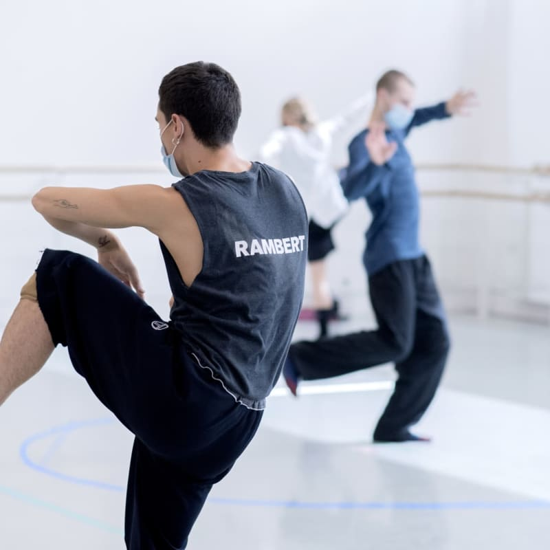 Three dancers from Rambert, dancing in a rehearsal space