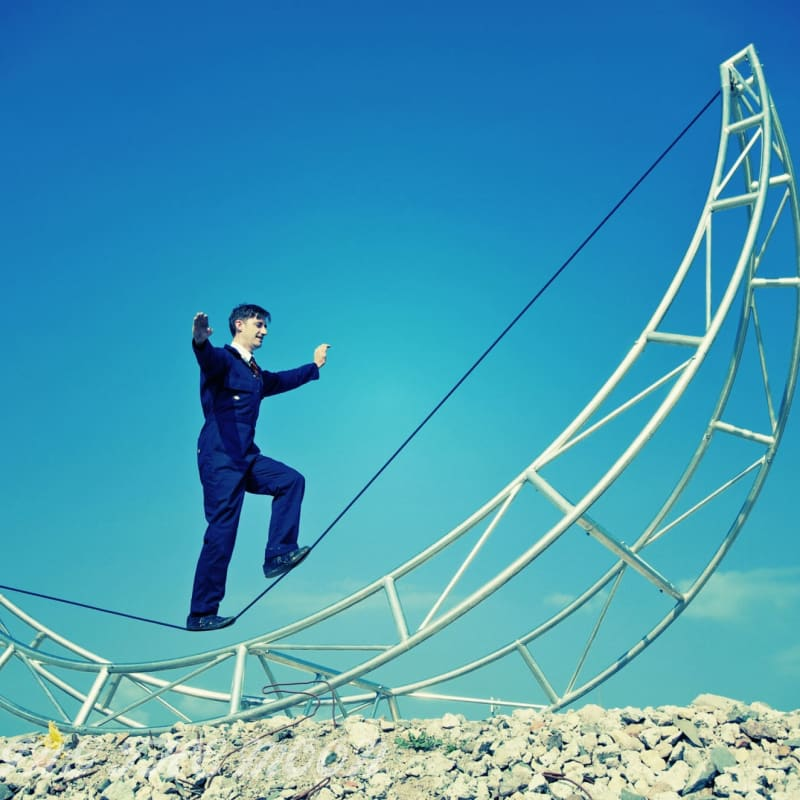 Acrobat walking on metal structure