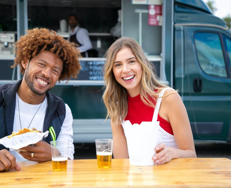 A smiling couple eating street food at a table