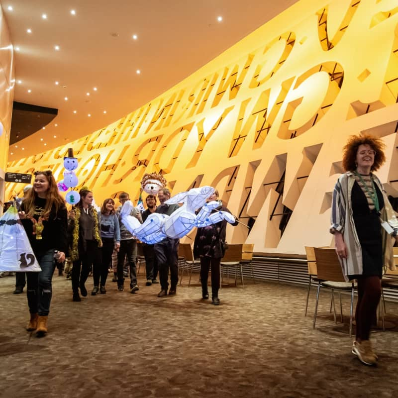 People parading with paper lanterns through a foyer at Wales Millennium Centre