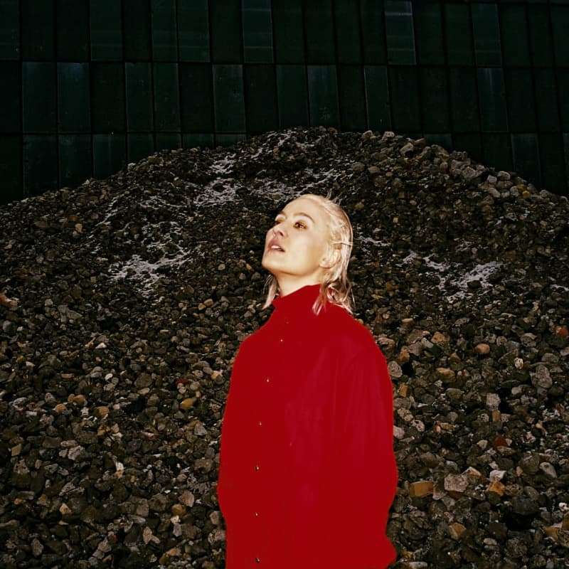Cate Le Bon stood outside wearing a red coat