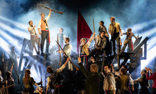 The cast of Les Misérables standing on the barricades stage set