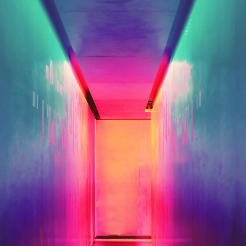Brightly lit corridor with neon pink and yellow lighting reflecting off the walls