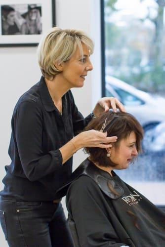 Karol et l'une de ses cliente en plein finition d'une coupe de cheveux