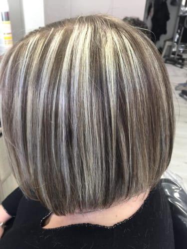 Des mèches blondes et grises sur des cheveux noirs