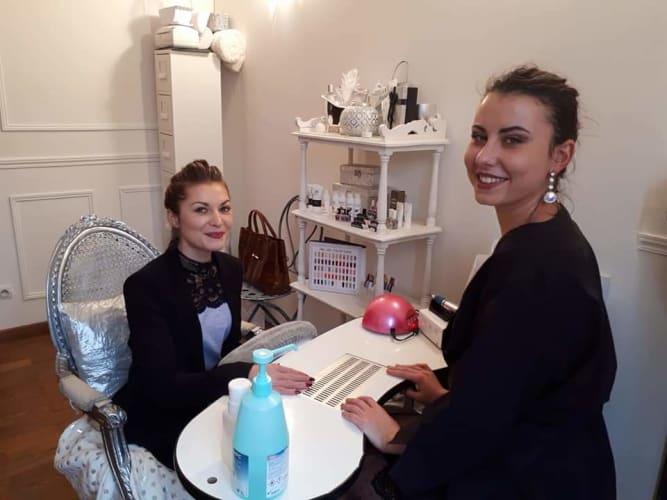 Notre jolie esthéticienne qui prend soin des ongles de l'une de nos clientes