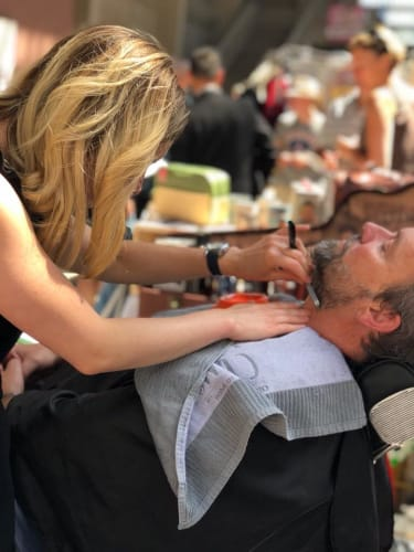 Notre barbière qui s'occupe de la barbe de l'un de nos clients
