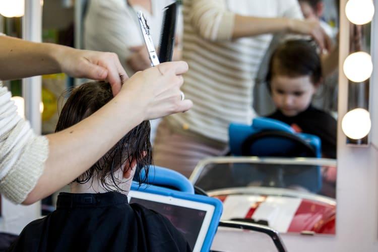 Un petit garçon entrain de se faire couper les cheveux par l'une de nos coiffeuses