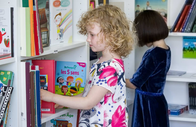 Une petit fille entrain de choisir un livre