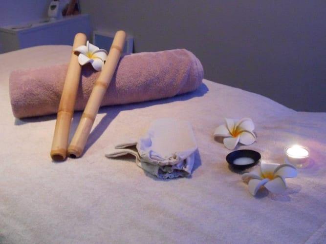 La table de la cabine de soins avec une serviette et des fleurs de tiaré, une ambiance exotique et relaxante