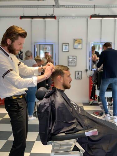 Un homme qui se fait couper les cheveux au salon Chez Max
