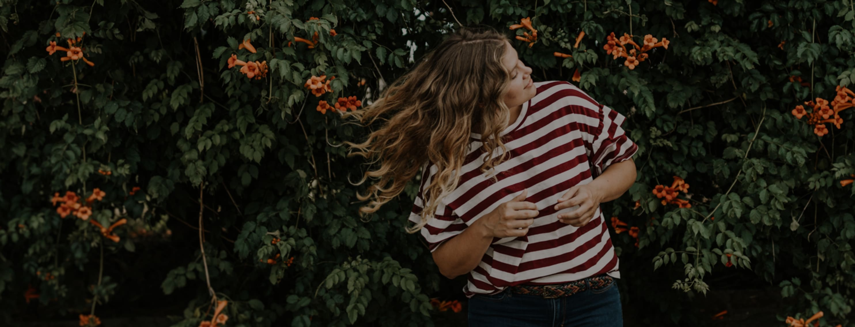 Woman with red and white striped shirt is flipping her hair.