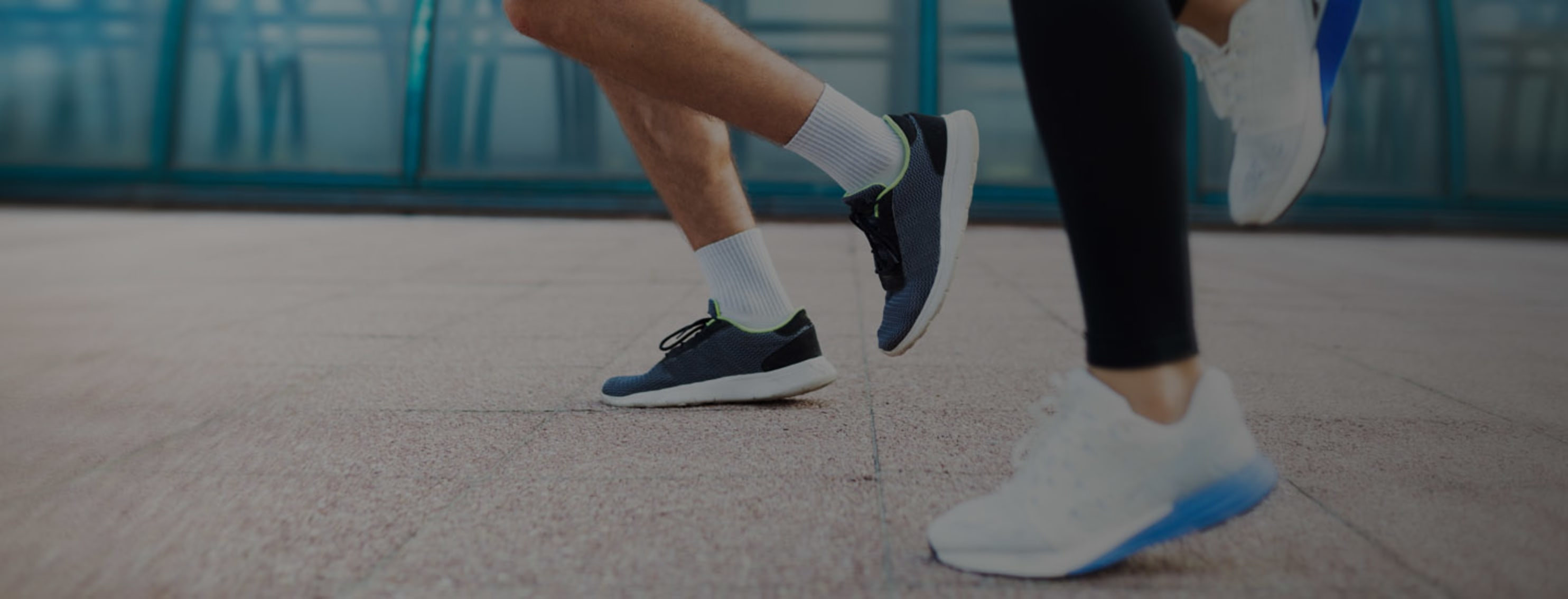 Two people running on pavement with focus on legs