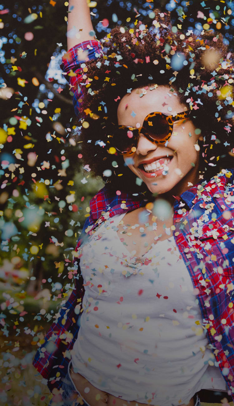 Happy women throwing up confetti