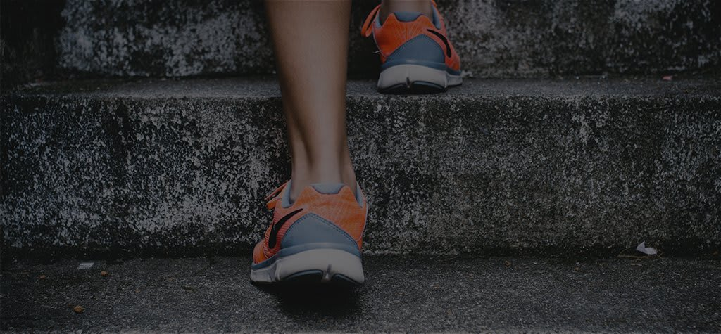 Legs in athletic shoes walking up stairs.