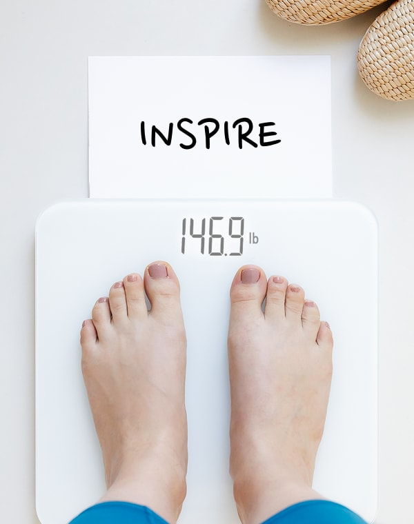 "Feet on a while scale with the weigh in word ""inspire"""