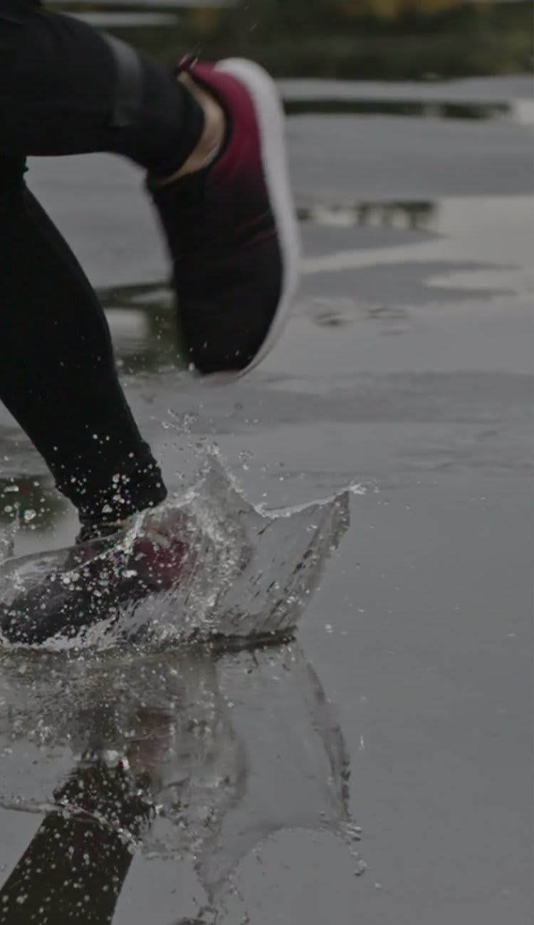Image of a woman running in puddles.