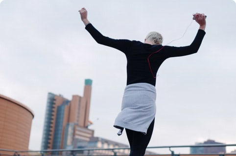 A lady with grey hair celebrating her success after a run.