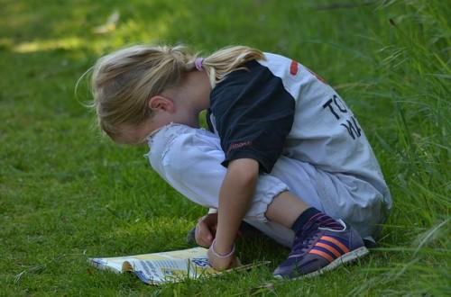 Criança com TDA lendo uma revista no gramado.