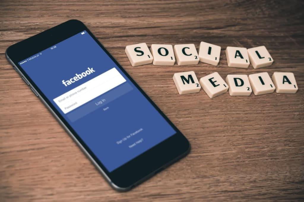 um celular logado no Facebook e a palavra social media ao lado, para ilustrar tipos de campanha para Facebook