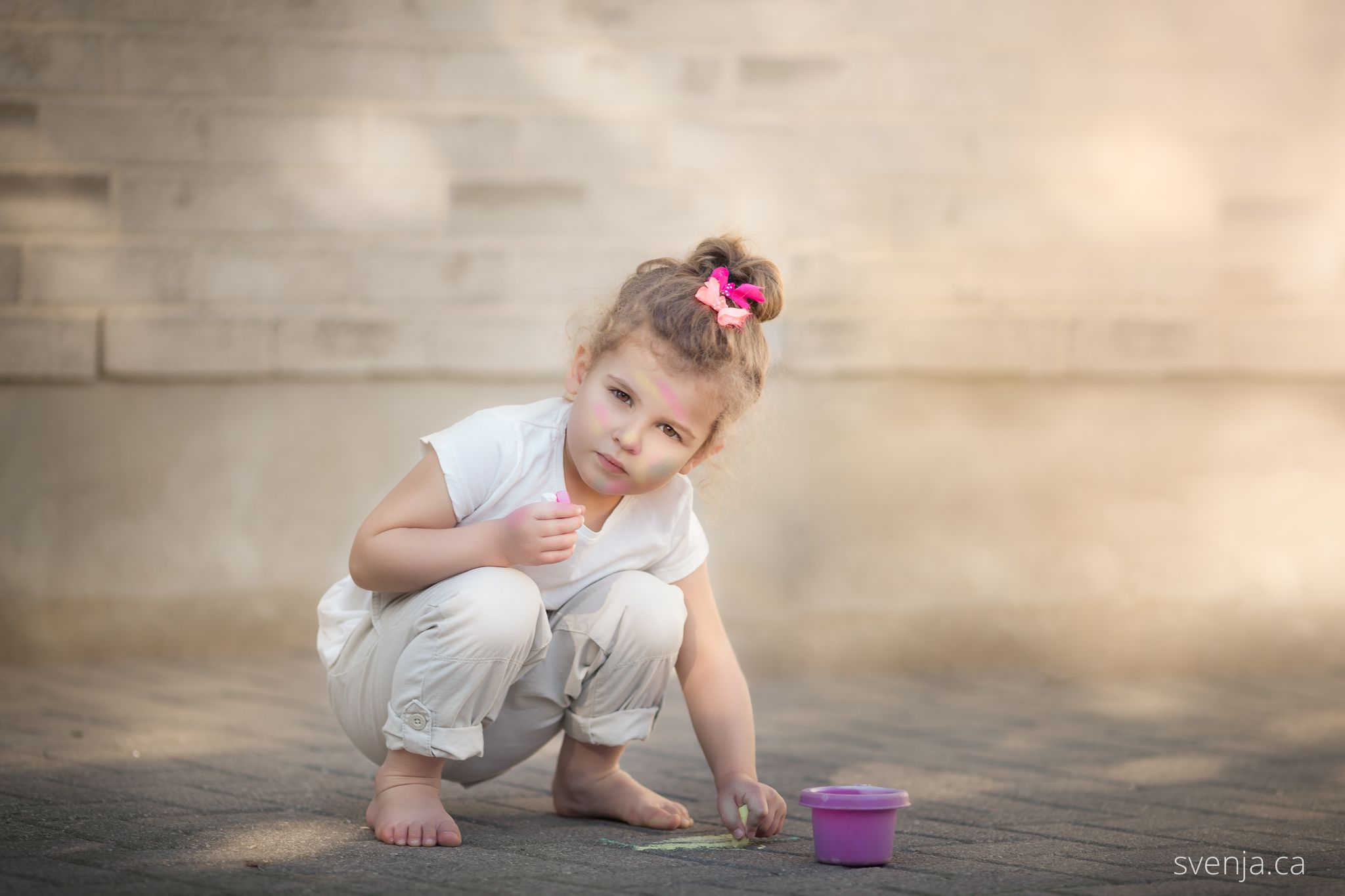 a little girl playing with sidewalk chalk