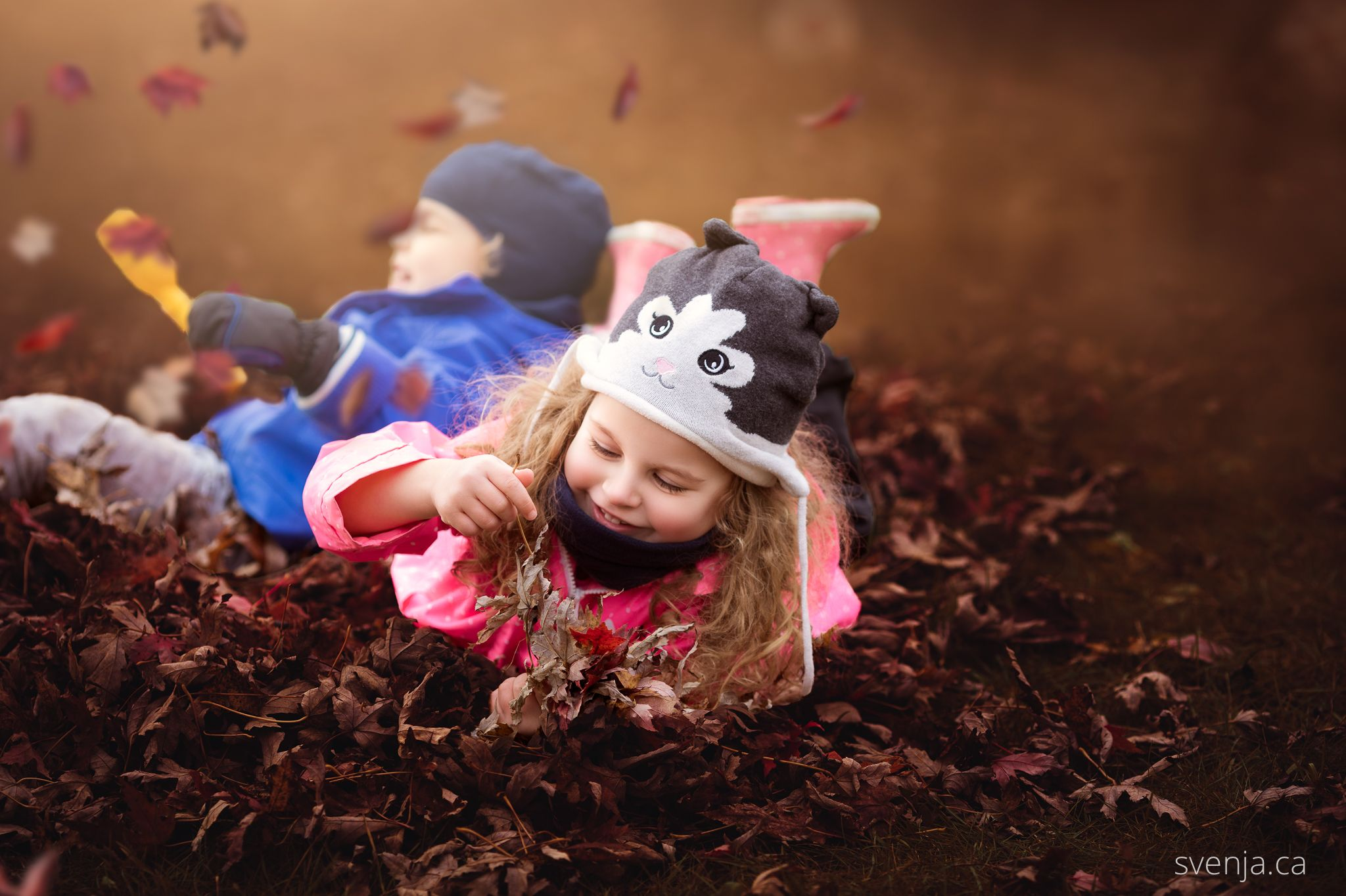 two young children playing with leaves in autumn