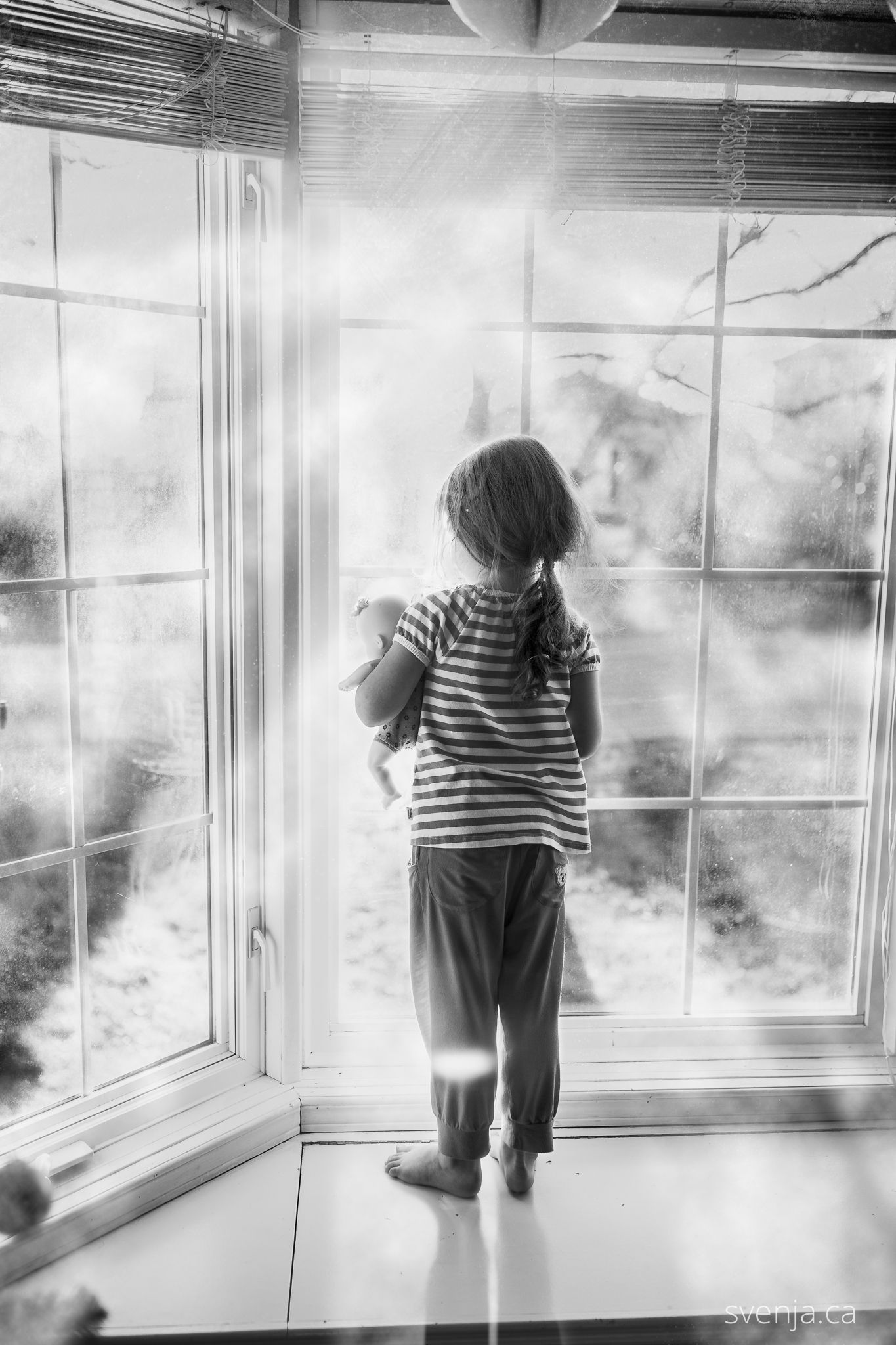 black and white picture of girl looking out the window holding her doll